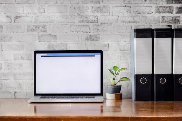 Espace de travail avec ordinateur portable et dossiers de fichiers sur la table en bois et mur de briques au bureau.