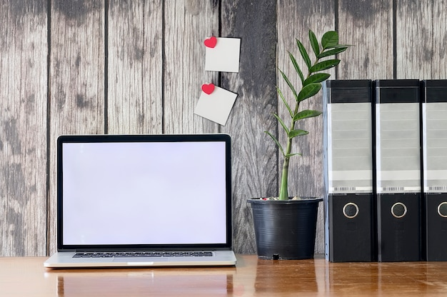 Espace de travail avec ordinateur portable et dossiers de fichiers sur la table en bois et le vieux mur en bois au bureau.