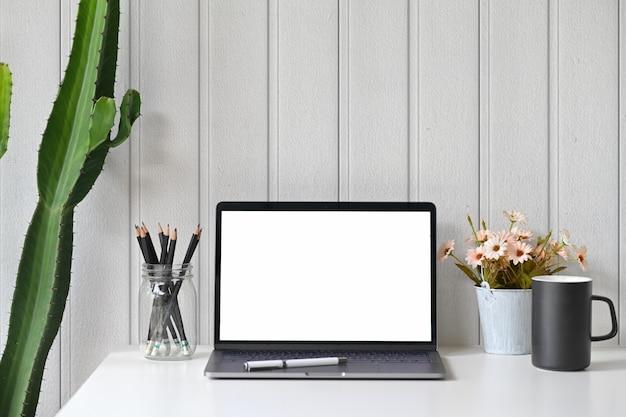 Espace de travail avec ordinateur portable à écran blanc.