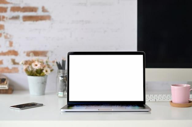 Espace de travail avec ordinateur portable à écran blanc