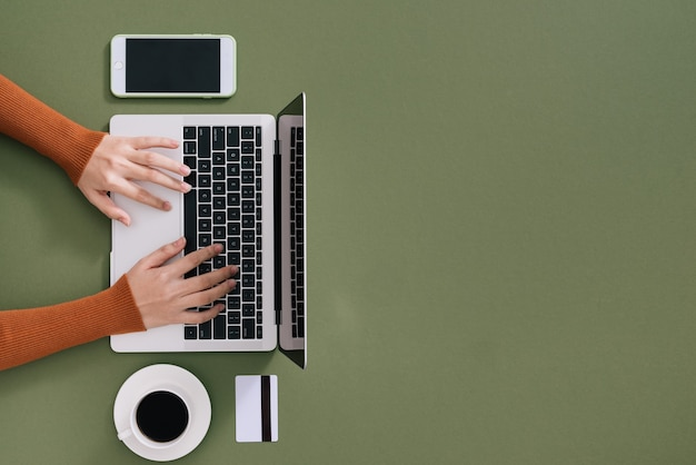 Espace de travail avec ordinateur portable, mains de la fille. ordinateur à plat
