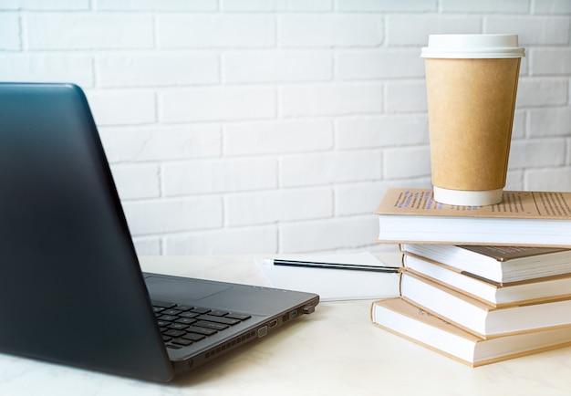 Espace de travail avec ordinateur portable moderne, livres, café et espace copie.