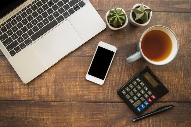 Espace de travail avec ordinateur portable et smartphone près d'une tasse de thé