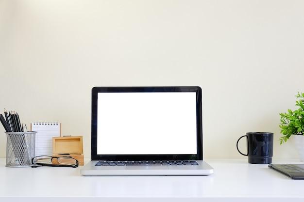 Espace de travail avec ordinateur portable sur la table blanche et l'espace maquette de fond jaune.