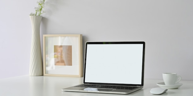 Un espace de travail ordonné est entouré d'un ordinateur portable à écran blanc, d'un cadre photo, d'une tasse à café et d'un vase de fleurs.