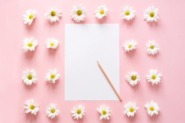 Espace de travail avec papier pour notes, fleurs de chrysanthème sur rose. mise à plat, vue de dessus.