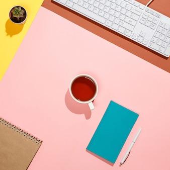 Espace de travail de pigiste moderne et coloré. composition plate de clavier, cactus, journal avec stylo et tasse de thé sur un bureau coloré. couleurs rose, jaune, aigue-marine et marron
