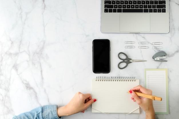 Espace de travail plat. main de femme avec une tasse de café, smartphone, ordinateur, ordinateur portable, planificateur et stationnaire avec espace copie