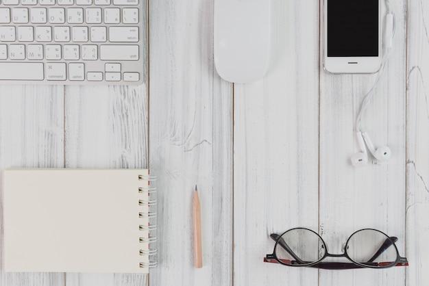 Espace de travail à plat, ordinateur, smartphone, ordinateur portable, crayon, lunettes sur table en bois blanc