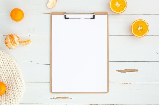 Espace de travail plat avec un presse-papiers sur des planches de bois blancs.