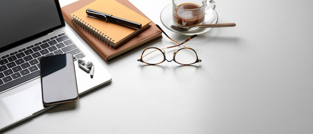 Espace de travail portable avec espace copie, smartphone, ordinateur portable, fournitures, tasse à café et livres de calendrier