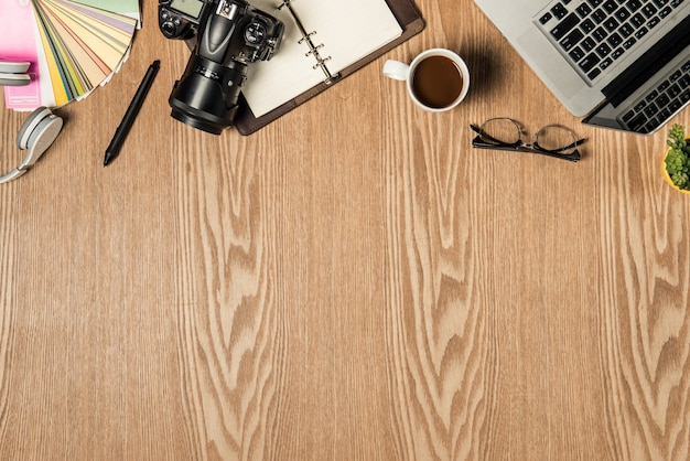 Espace de travail pour photographe, graphiste. mise à plat d'un ordinateur portable, d'un appareil photo, d'un nuancier, d'une tablette numérique, d'une tasse à café, d'un livre, d'un crayon sur une table en bois.