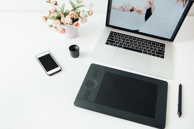 Espace de travail de retoucheur professionnel. ordinateur portable, pot de fleur, stylet et tablette pour la retouche. espace de travail de retoucheur professionnel.