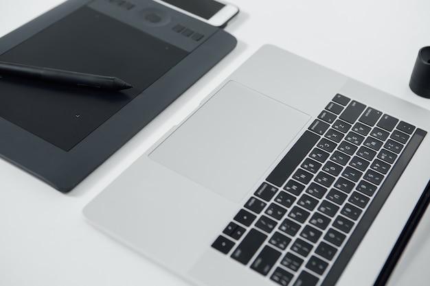 Espace de travail de retoucheur professionnel. ordinateur portable, stylet et tablette pour la retouche. espace de travail de retoucheur professionnel.