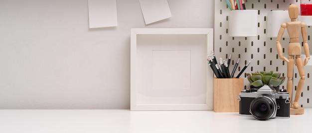 Espace de travail simple avec espace de copie, cadre de maquette, appareil photo, papeterie et décorations