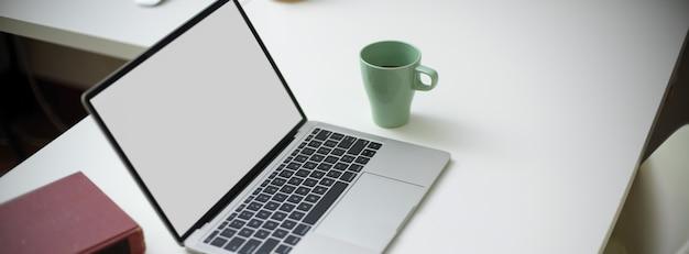 Espace de travail simple avec ordinateur portable, tasse, espace de copie de livre sur table blanche avec chaise