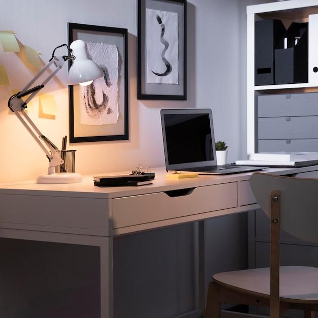 Espace de travail soigné et bien rangé avec ordinateur portable et lampe