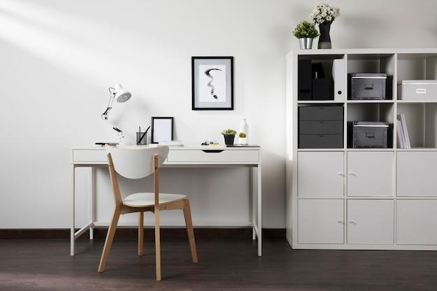 Espace de travail soigné et organisé avec chaise et lampe