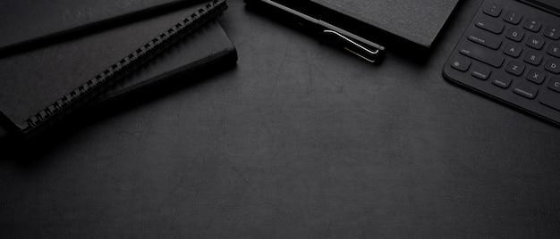 Espace de travail sombre de luxe avec livres de calendrier, stylo, tablette numérique avec clavier et espace de copie