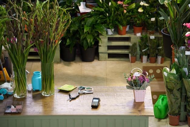 Espace de travail de table de fleuriste avec des ciseaux pour créer des bouquets à l'intérieur du magasin de fleurs avec des plantes en pots