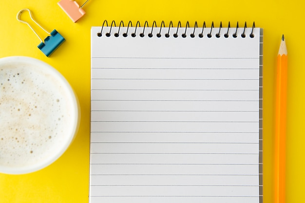 Espace de travail, table de travail. cahier ouvert, tasse à café et fournitures de bureau. lay plat, espace de copie.