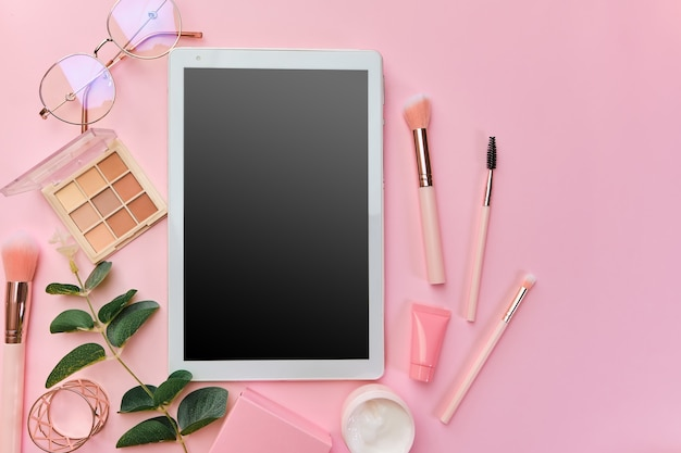 Espace de travail avec tablette blanche, bloc-notes, lunettes, stylos, accessoires de beauté, clavier, fournitures de bureau, feuille verte sur surface rose