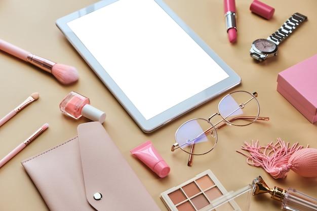 Espace de travail avec tablette blanche, bloc-notes, lunettes, stylos, accessoires de beauté sur une surface beige pastel
