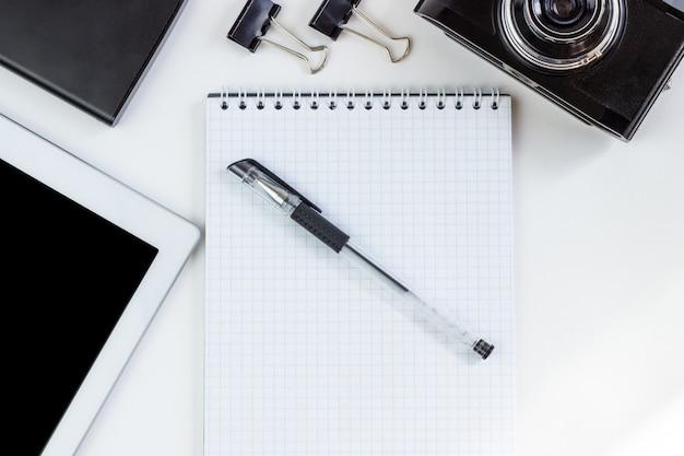 Espace de travail avec tablette, bloc-notes, appareil photo, disque dur externe situé sur une table blanche,