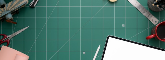 Espace de travail avec tablette, ciseaux, fournitures et espace de copie sur tapis de découpe