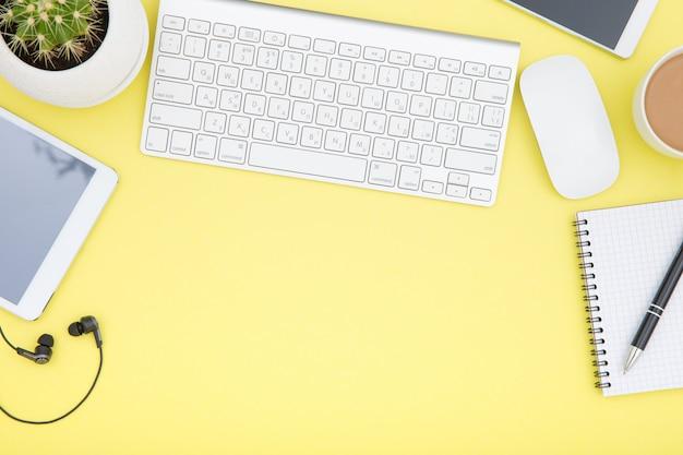 Espace de travail avec tablette, clavier, tasse à café et lunettes copie l'espace sur fond jaune.