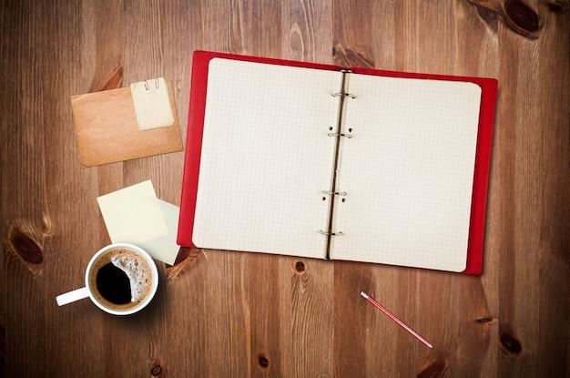 Espace de travail avec tasse à café, photos instantanées, papier à lettres et cahier sur la vieille table en bois