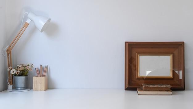 Espace de travail vintage avec cadre, crayons, plante en pot, tasse à café, lampe et vieux livre sur table blanche.
