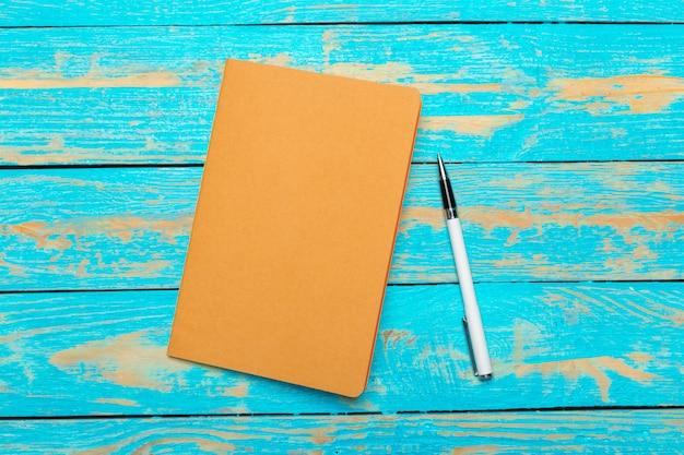 Espace de travail vue de dessus avec bloc-notes vierge et stylo sur fond de table en bois