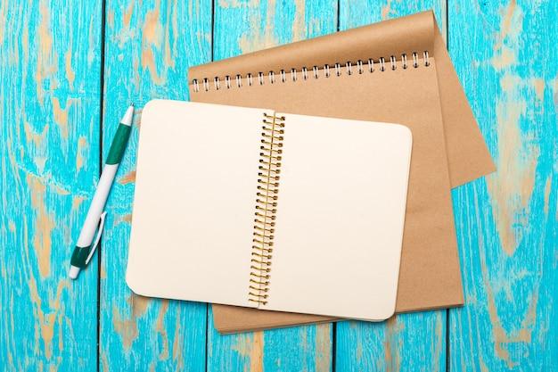 Espace de travail vue de dessus avec un cahier vierge et un stylo sur fond de table en bois