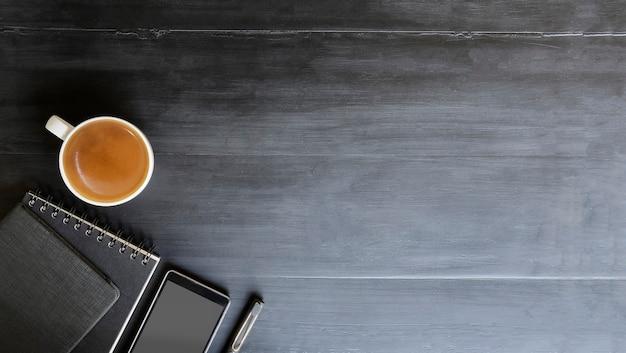 Espace de travail vue de dessus espace copie avec livre et stylo tasse de café sur un bureau noir
