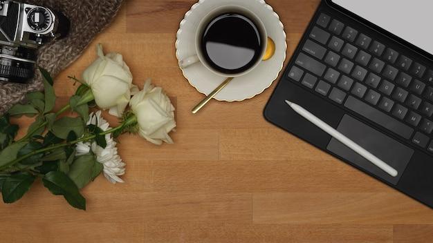 Espace de travail vue de dessus avec tablette, clavier, tasse à café et fleur