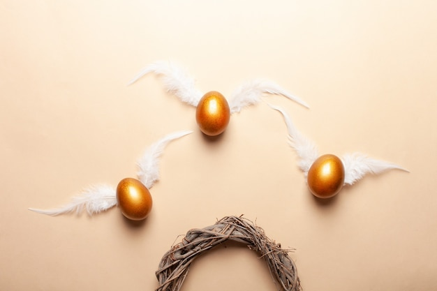 Espace vide pour le texte, une bannière de joyeuses pâques. œufs dorés peints, plumes blanches.