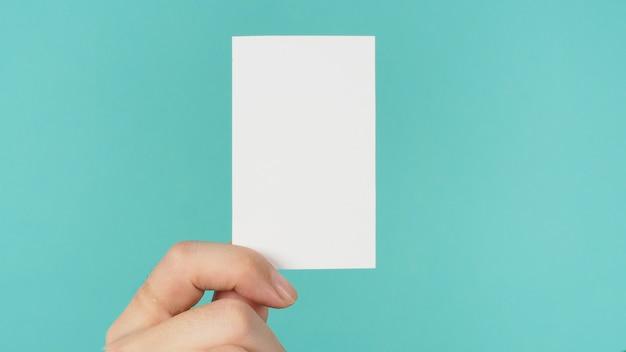 Espace vide pour le texte. main masculine tenant une carte vierge blanche isolée sur fond vert menthe ou bleu tiffany.