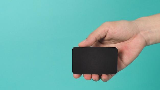 Espace vide pour le texte. main masculine tenant une carte vierge noire isolée sur fond vert menthe ou bleu tiffany.