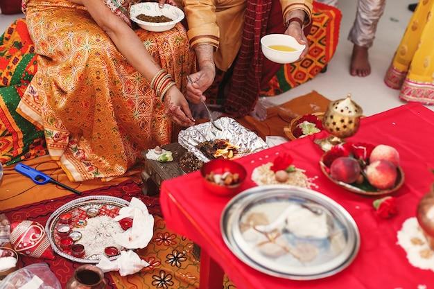 Les espèces et les fruits entourent les parents indiens préparant la pâte