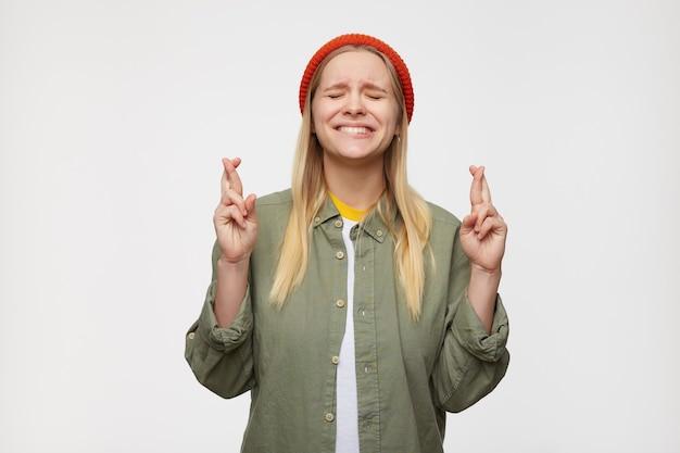 En espérant que jeune femme blonde aux cheveux longs au chapeau rouge et des vêtements décontractés gardant les yeux fermés tout en faisant des vœux et en croisant les doigts pour la bonne chance, posant sur le bleu