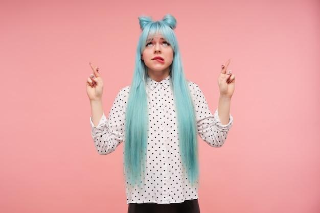 En espérant que jeune femme séduisante aux cheveux bleu anime à la recherche décomposée vers le haut et mordant la lèvre inférieure, croisant les doigts pour la bonne chance tout en posant