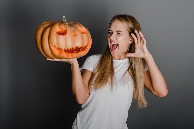 Espiègle jeune femme avec citrouille halloween jack o lantern isolée sur gris