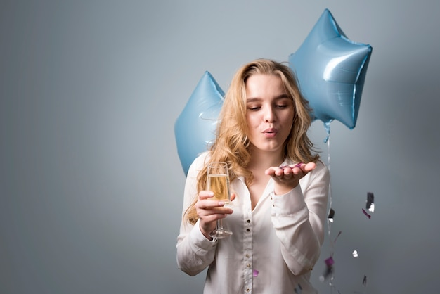 Espiègle jeune femme soufflant des confettis