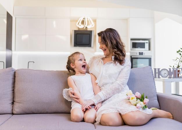 Espiègle mère et fille se regardant assis sur un canapé