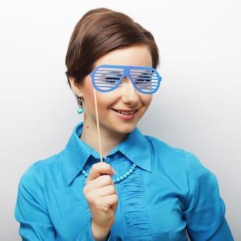 Espiègles jeunes femmes tenant une fête lunettes