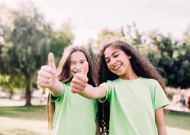 Espiègles petites filles gesticulant pouce en haut signe