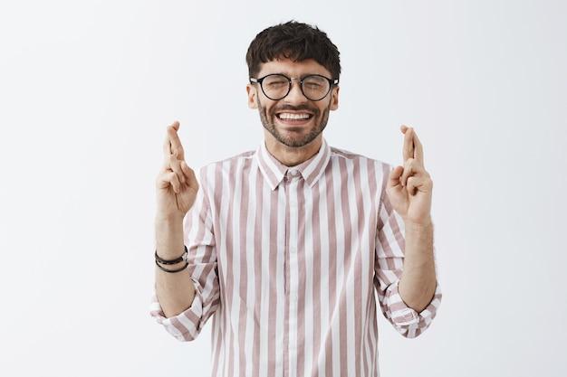 Espoir élégant barbu posant contre le mur blanc avec des lunettes