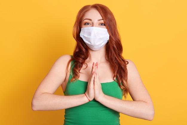 Espoir jeune femme en masque médical parler à dieu, prier et tenir la main, vêtu d'un t-shirt vert, femme aux cheveux rouges contre le mur jaune.