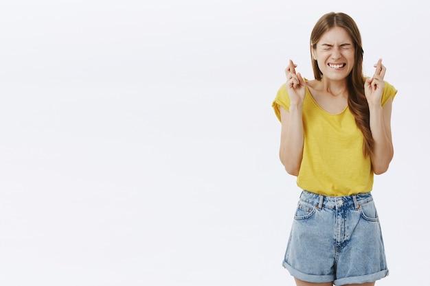 Espoir jolie fille à la recherche inquiète et nerveuse, faisant un souhait avec les doigts croisés